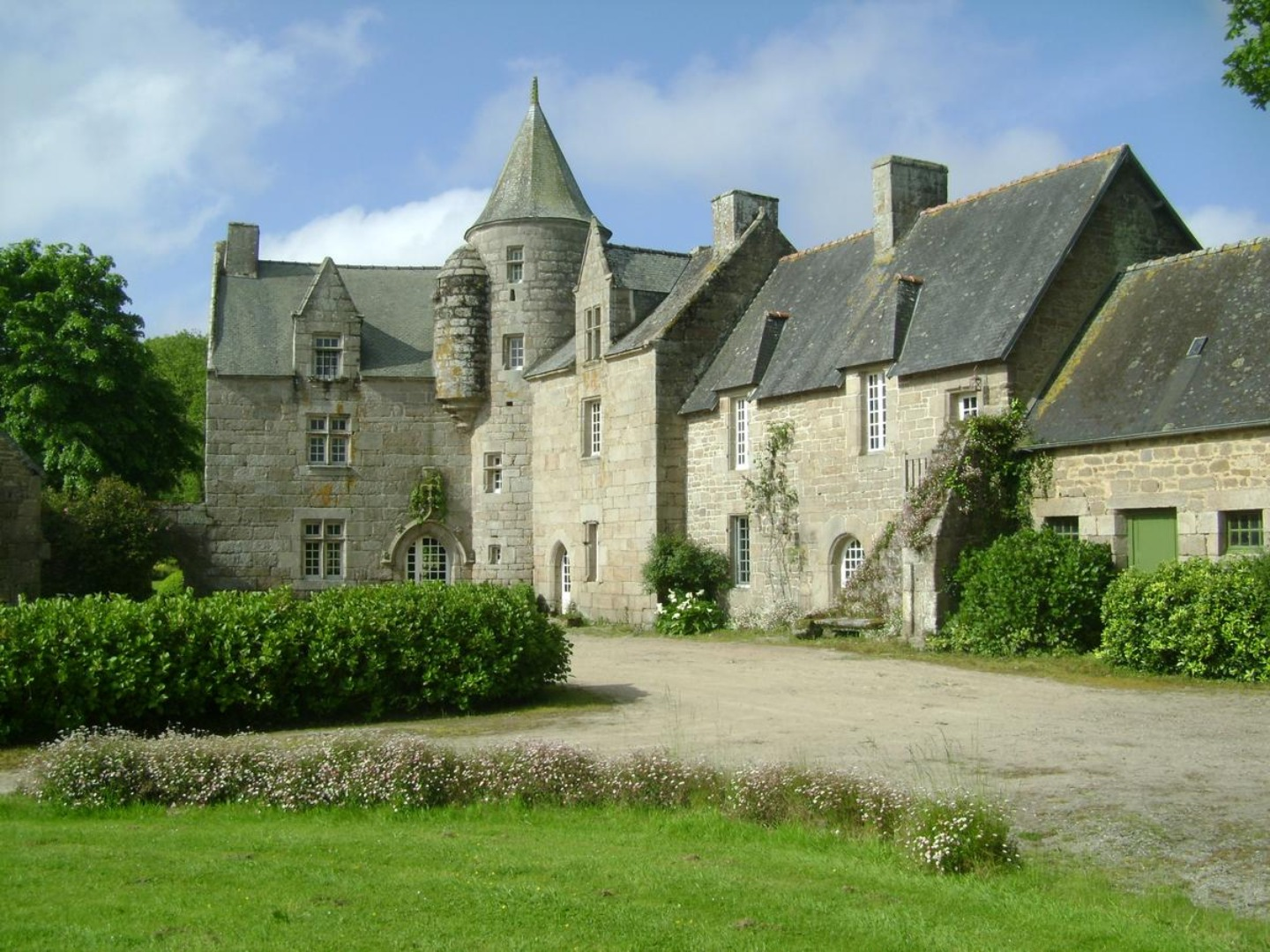 A stone castle next to a brick building at Manoir de Kerguereon.