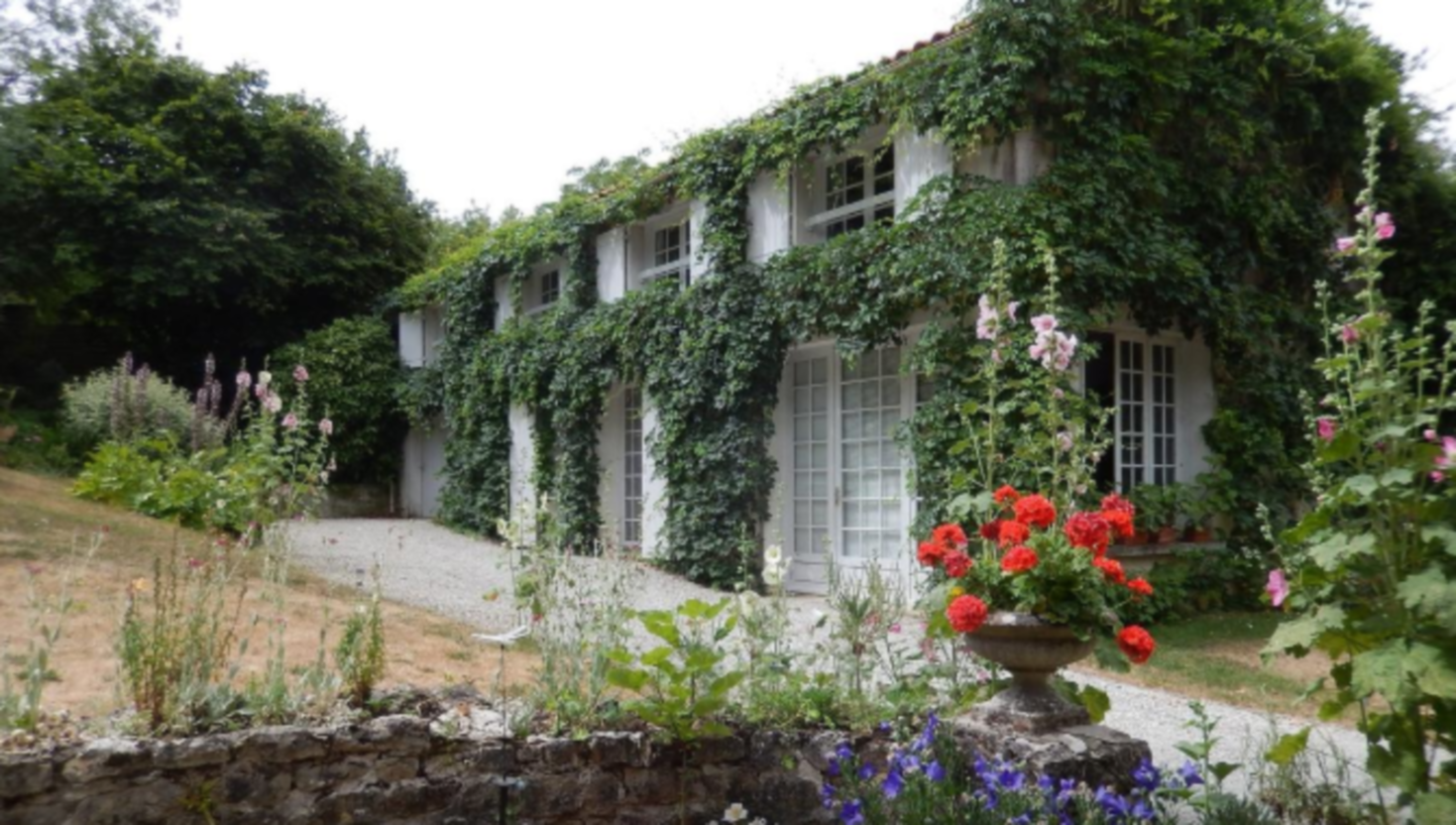 A house with bushes in front of a building at Le Petit Massigny.
