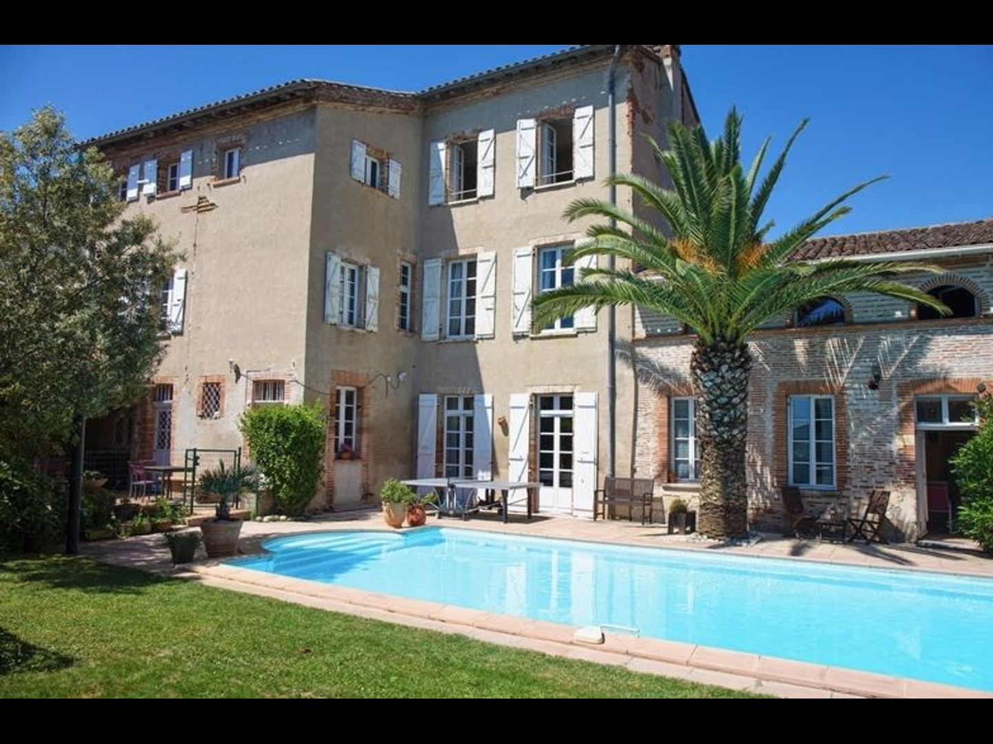 A house with a pool in front of a building at Maison Joséphine - chambres d'hôtes.