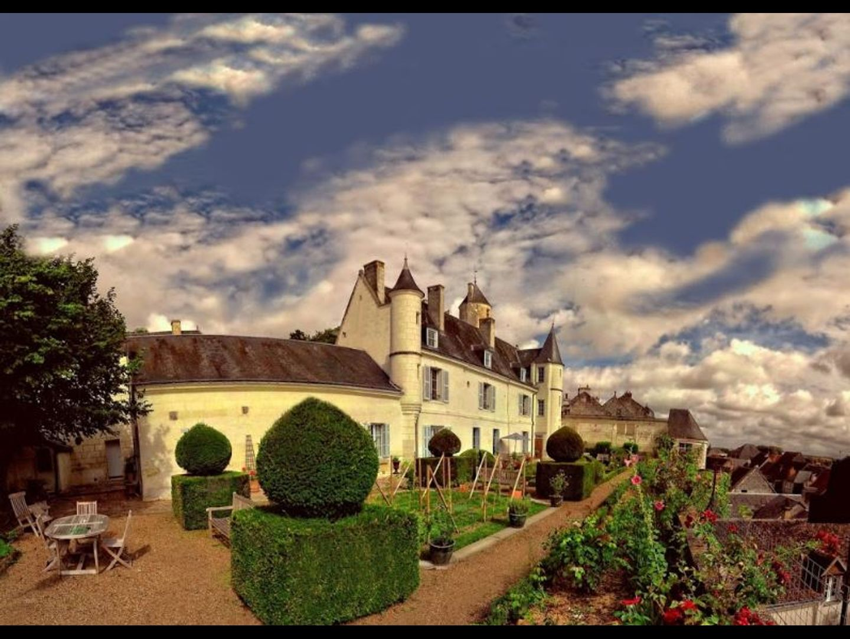 A house with a cloudy sky at La Maison de l'Argentier du Roy.