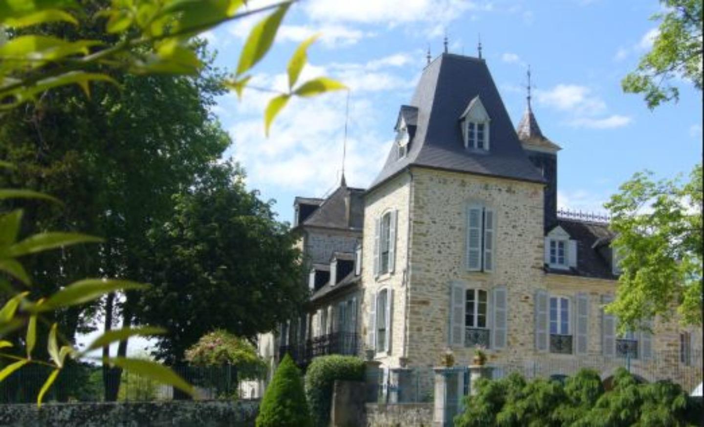 A small clock tower in front of a house at Domaine de Larrey, situé aux pieds des Pyrénées.