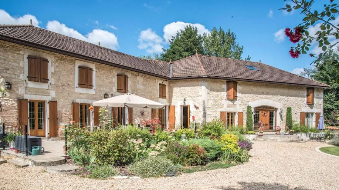 A large brick building with grass in front of a house at Moulin du Fontcourt Chambre d'Hotes.