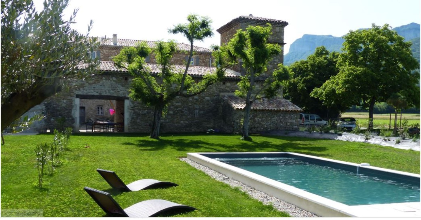 A large lawn in front of a pool at LA BELLE ETOILE.