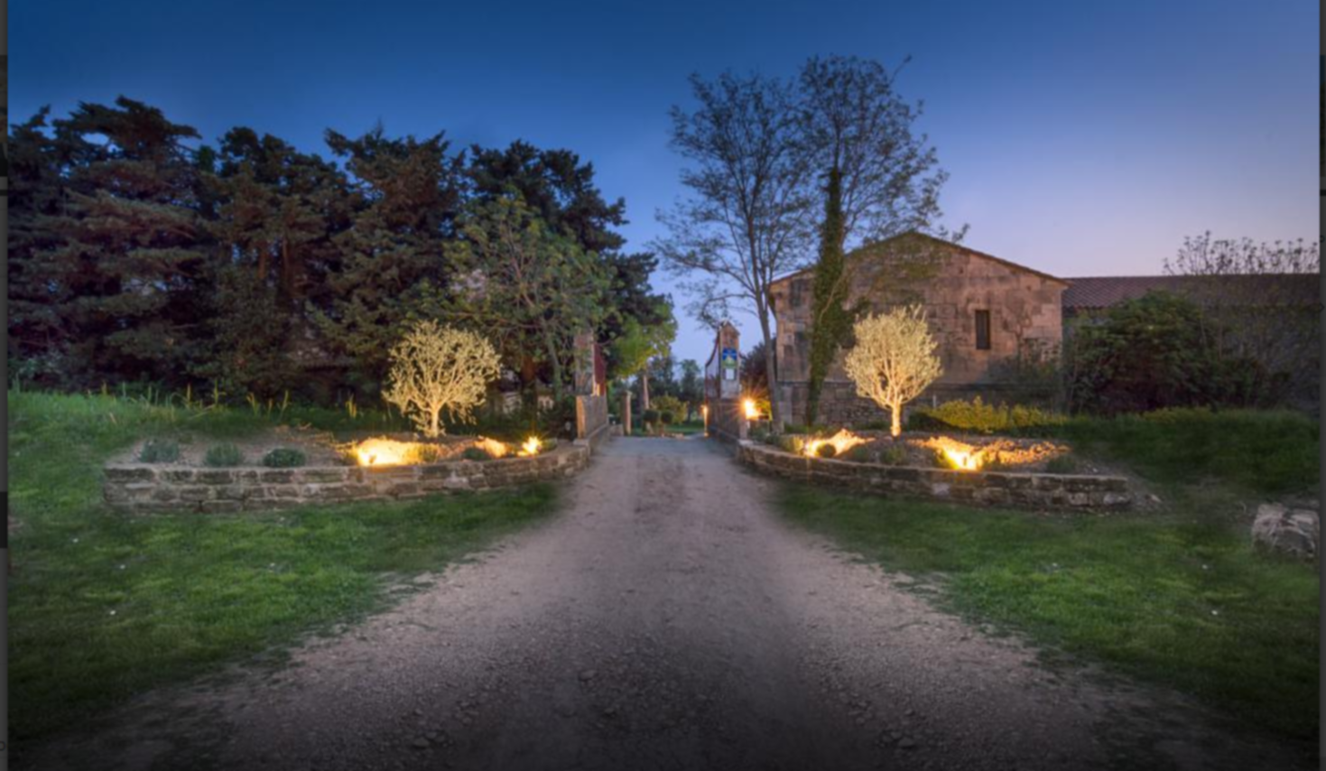 A path with grass in front of a house at Le Mas d'Eymard.