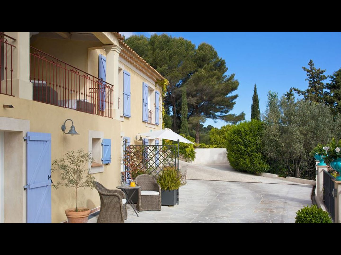 """A house with trees in the background at Villa """"Le Port d'attache""""."""
