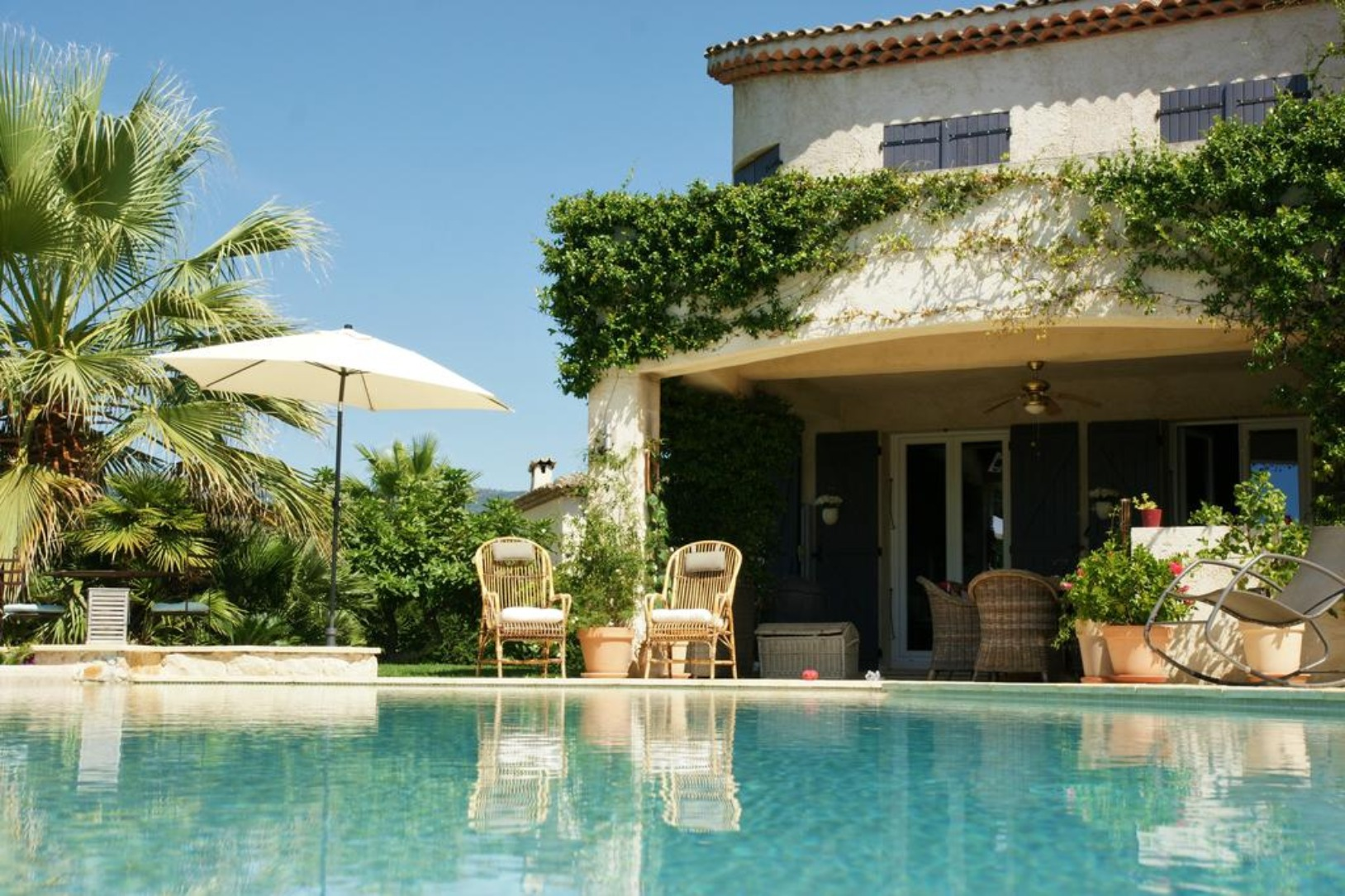 A pool next to a palm tree at Chambre d'hôtes d'Isabelle.
