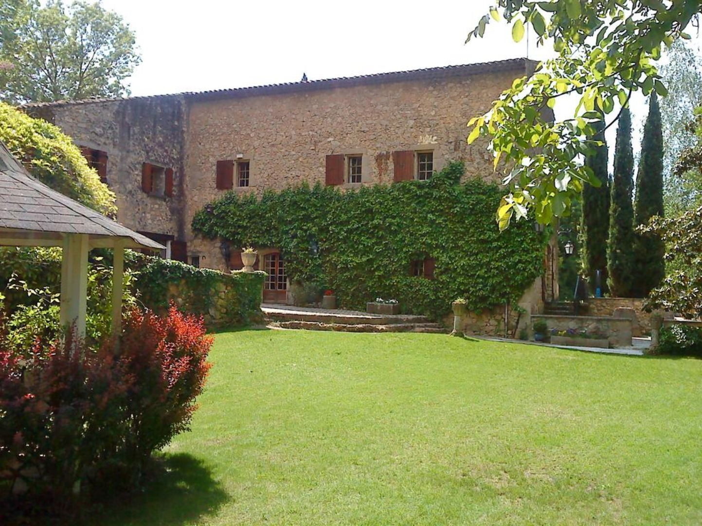 A large brick building with grass and trees at Le Vieux Moulin.