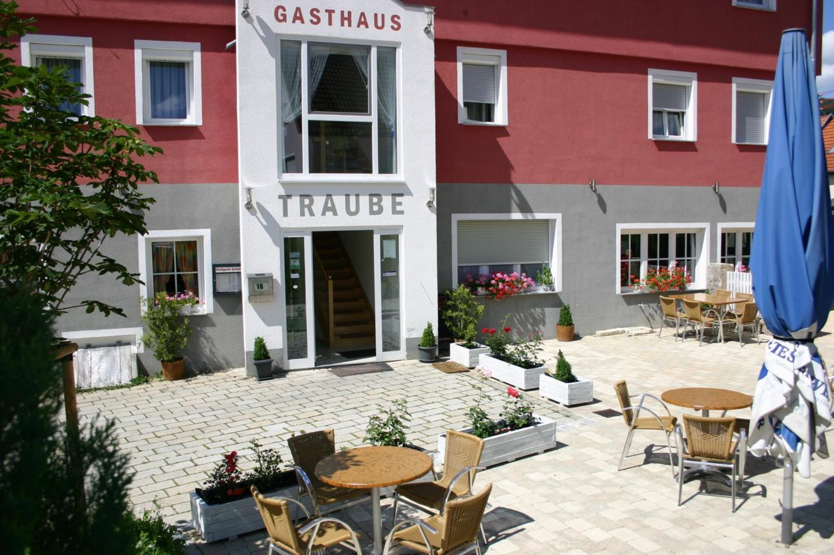 A person standing in front of a house at Gasthaus Traube.
