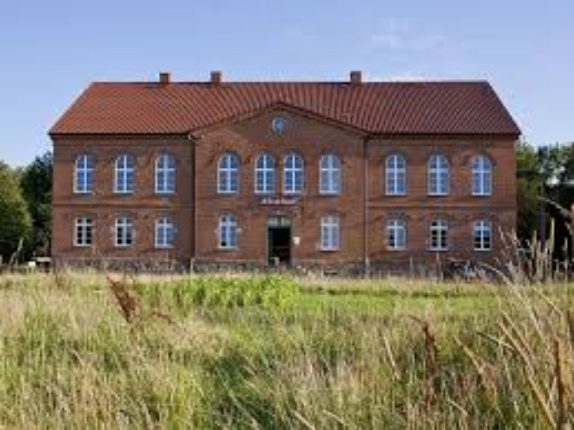 A large brick building with a grassy field at Kranich Hotel.