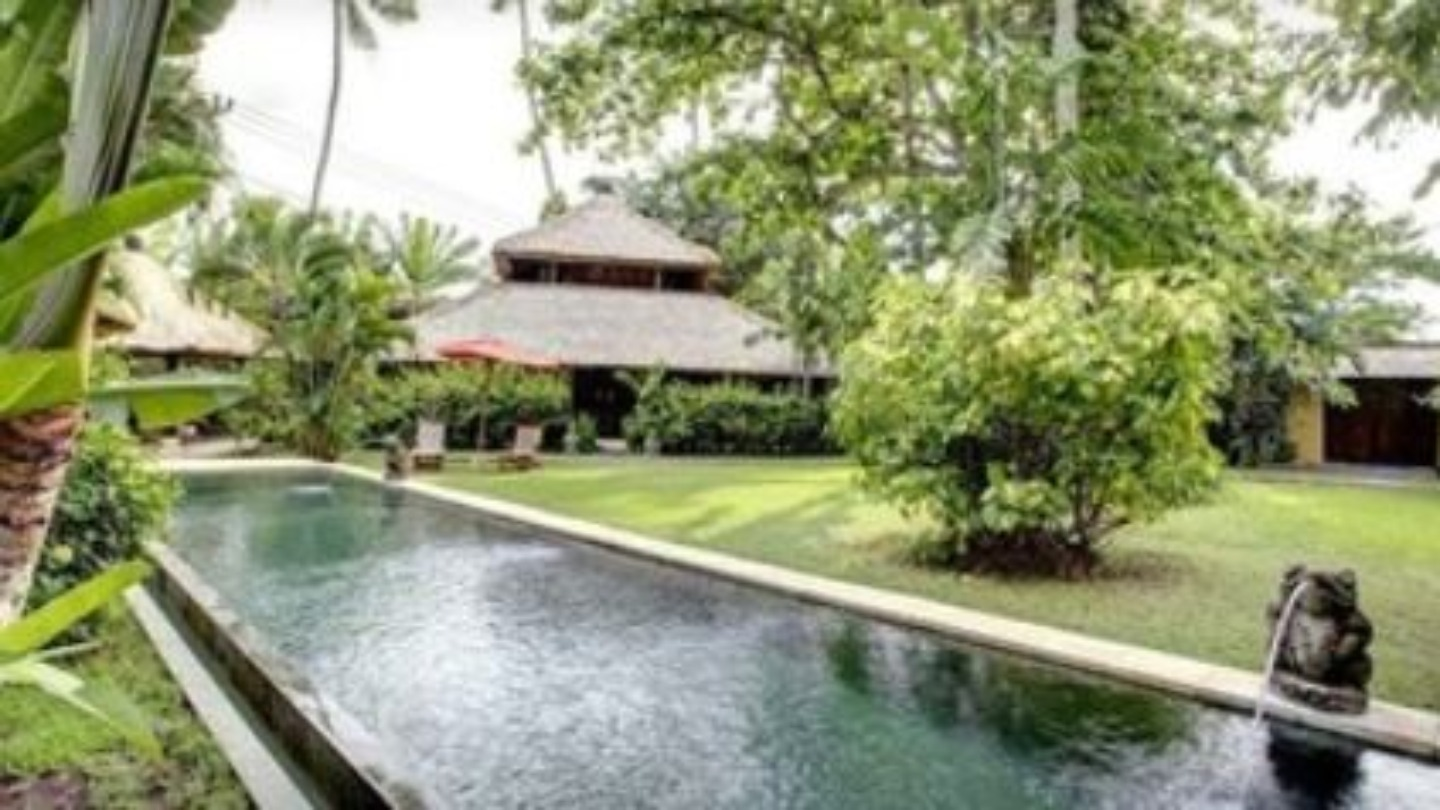 A garden with water in the background at Bali Villa Kelapa.