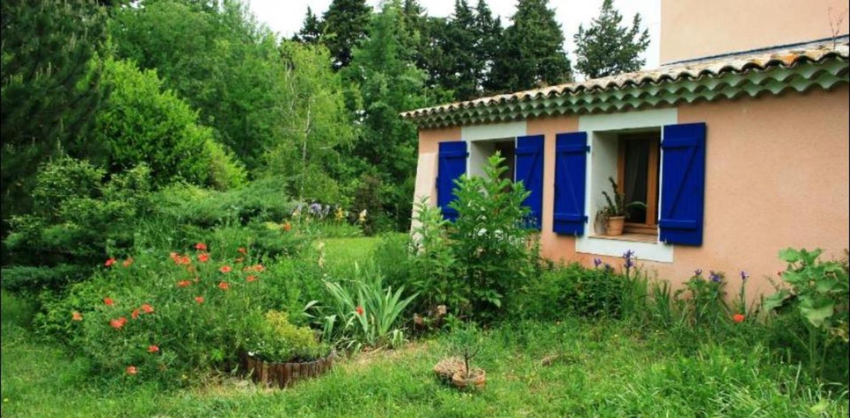 A house with bushes in front of a building at Le Mas de la Cigale Bleue.