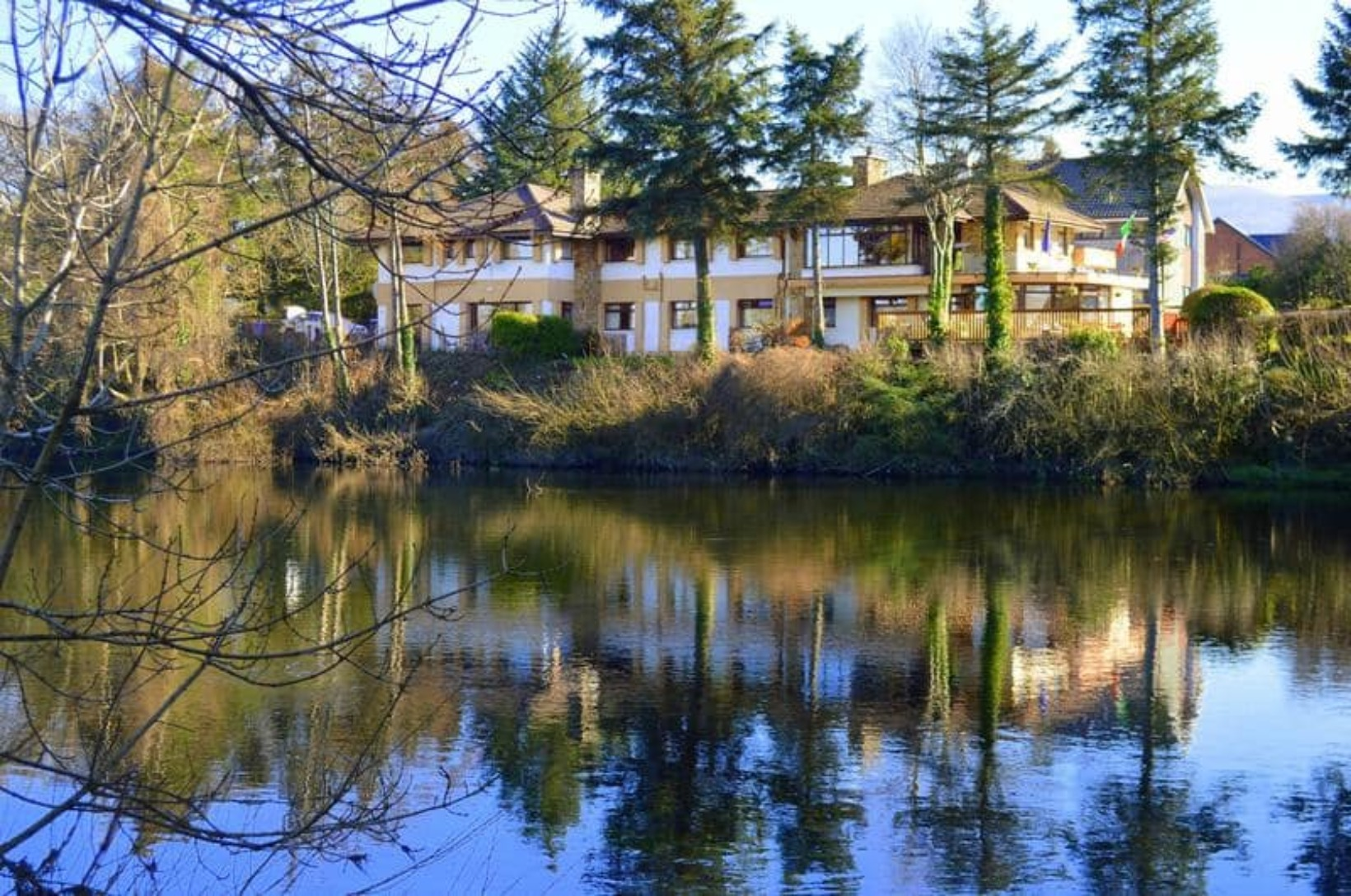 A body of water surrounded by trees at Killarney View House.
