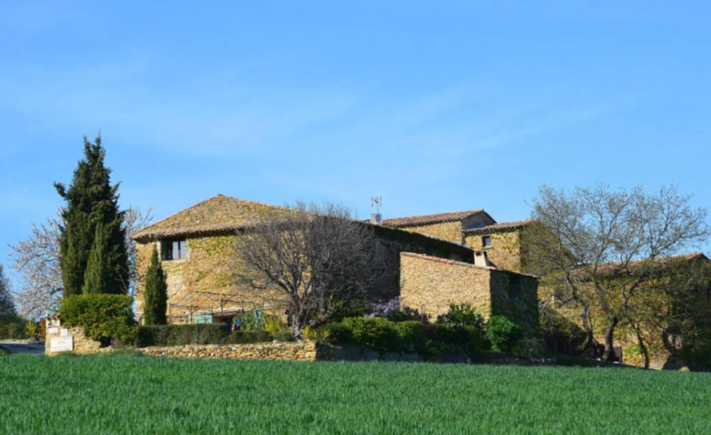 A large brick building with a grassy field at LES GRANDES MOLLIERES.