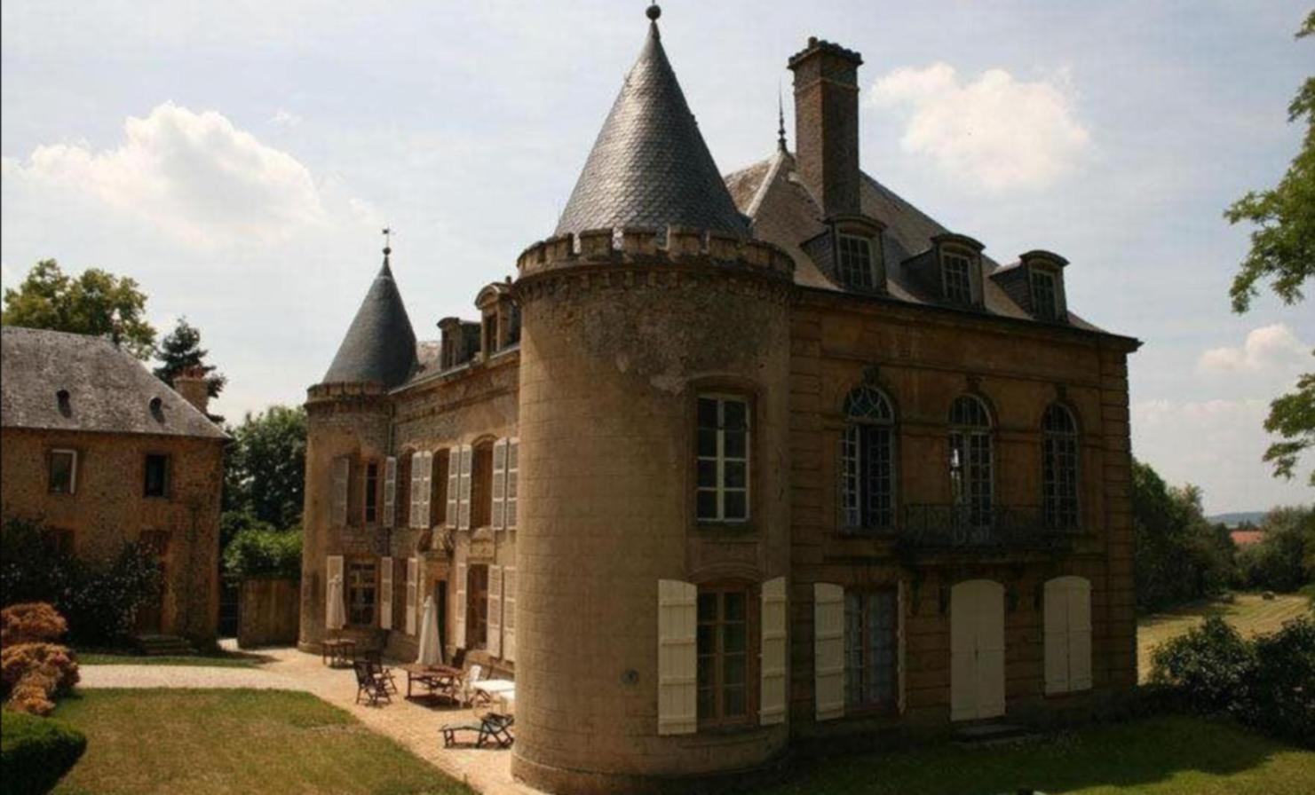 A large brick building with a clock tower at Chateau de villette.