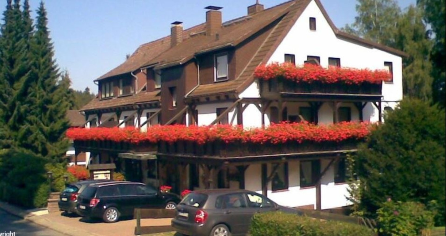A car parked on the side of a building at Hotel Haus Ingeburg.