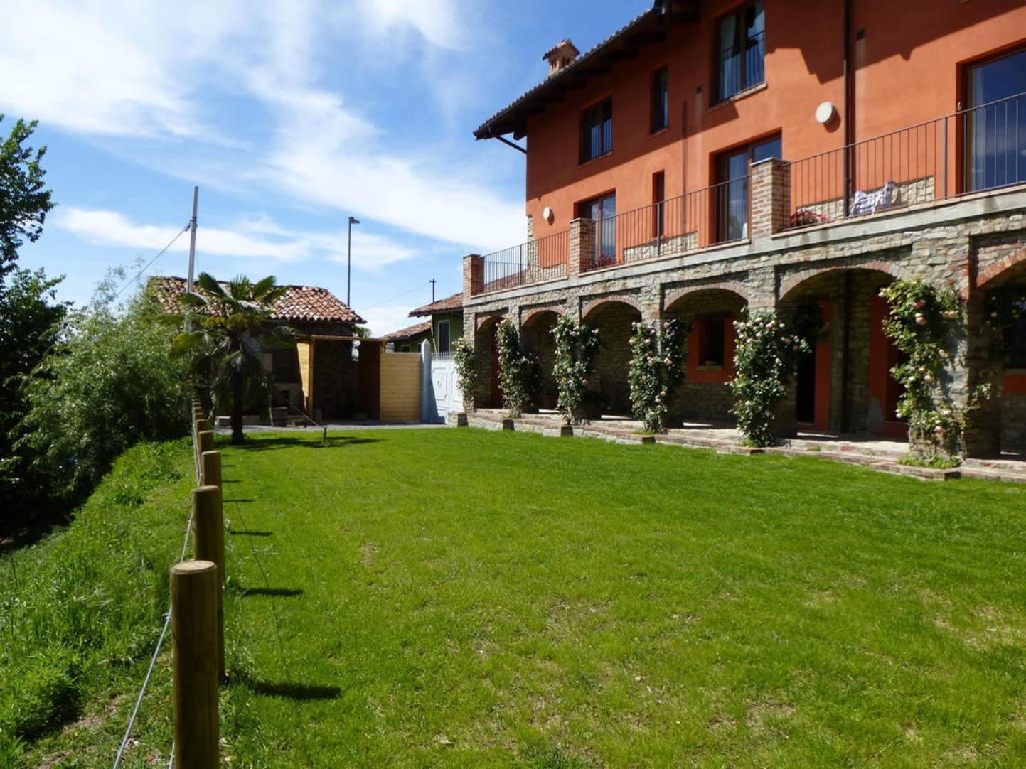 A large brick building with green grass at La Corte Di Langga.