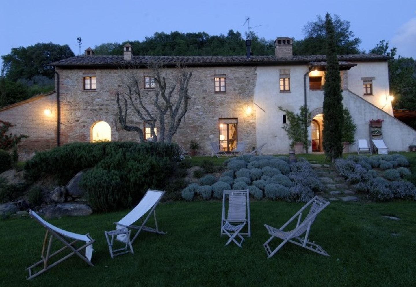 A large lawn in front of a house at Podere Poggio al Sole.