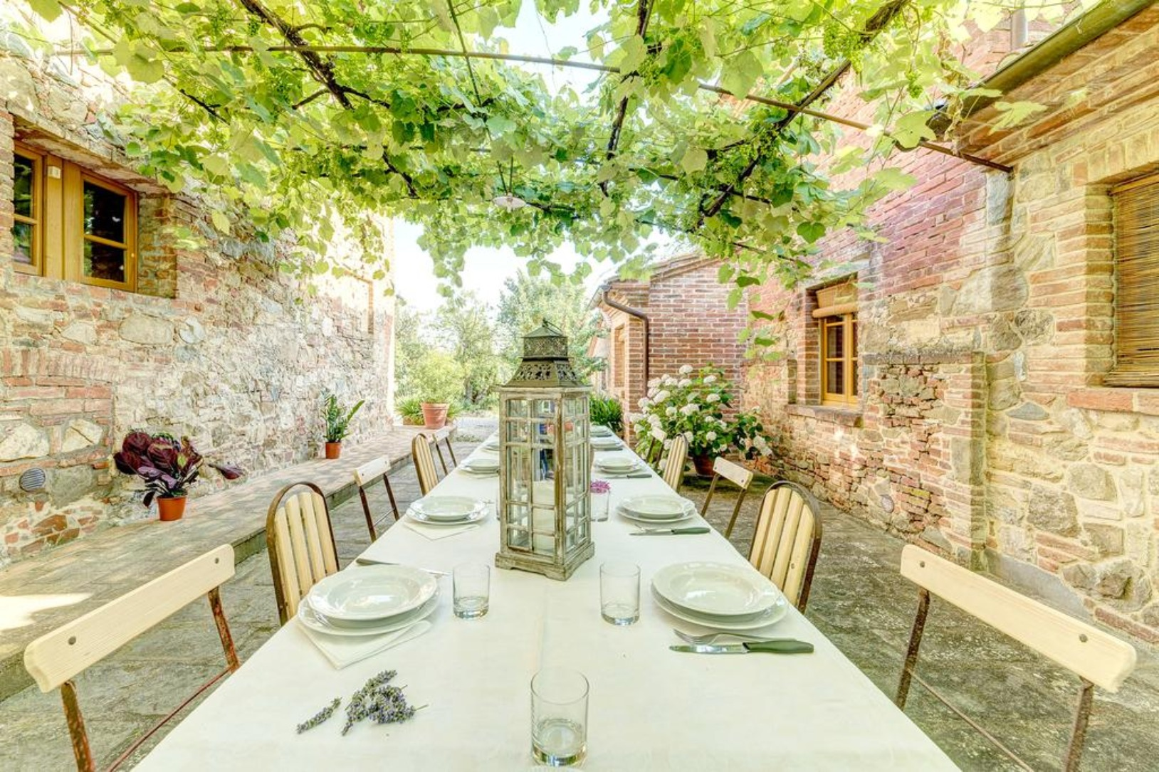 A dining table in front of a brick building at Agriturismo Menchetti.