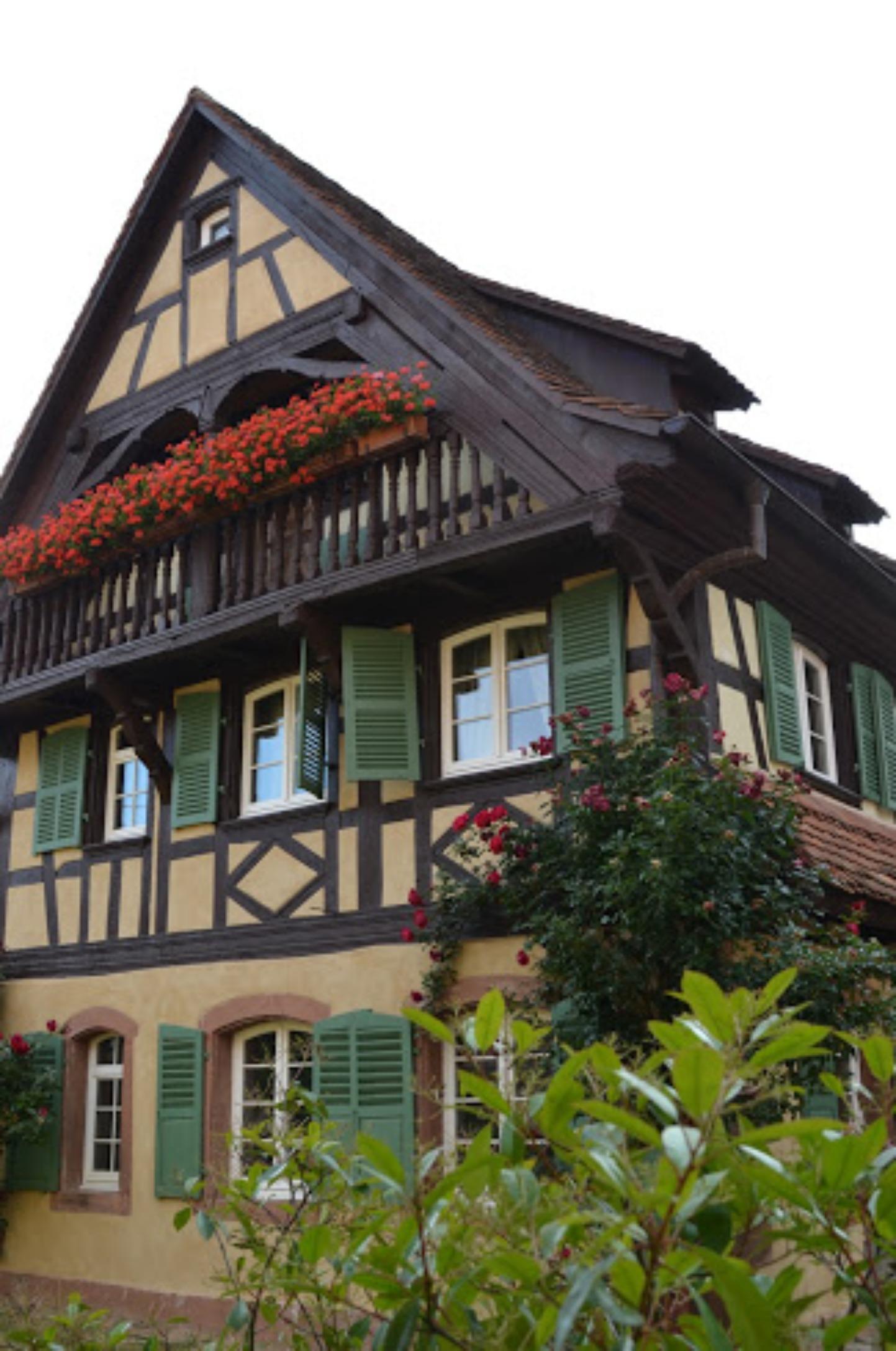 A house that has a sign on the side of a building at Maison d'hôtes Au fil du temps.