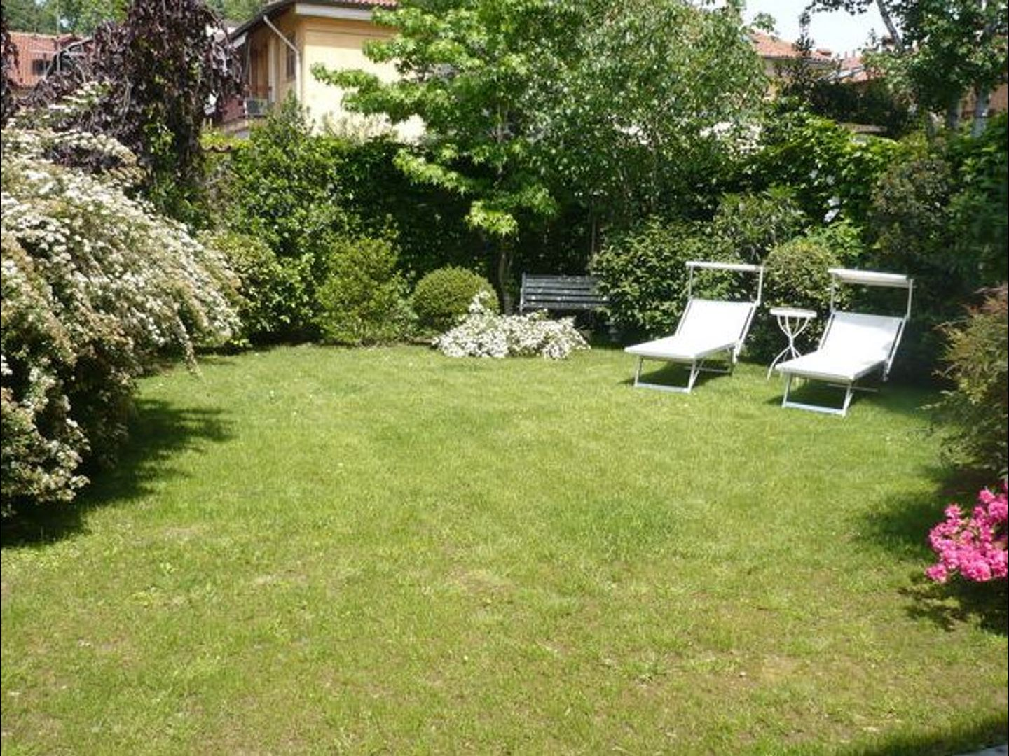 """A couple of lawn chairs sitting on top of a lush green field at B&B of """"I BRAVI"""" - Charming Guest House."""