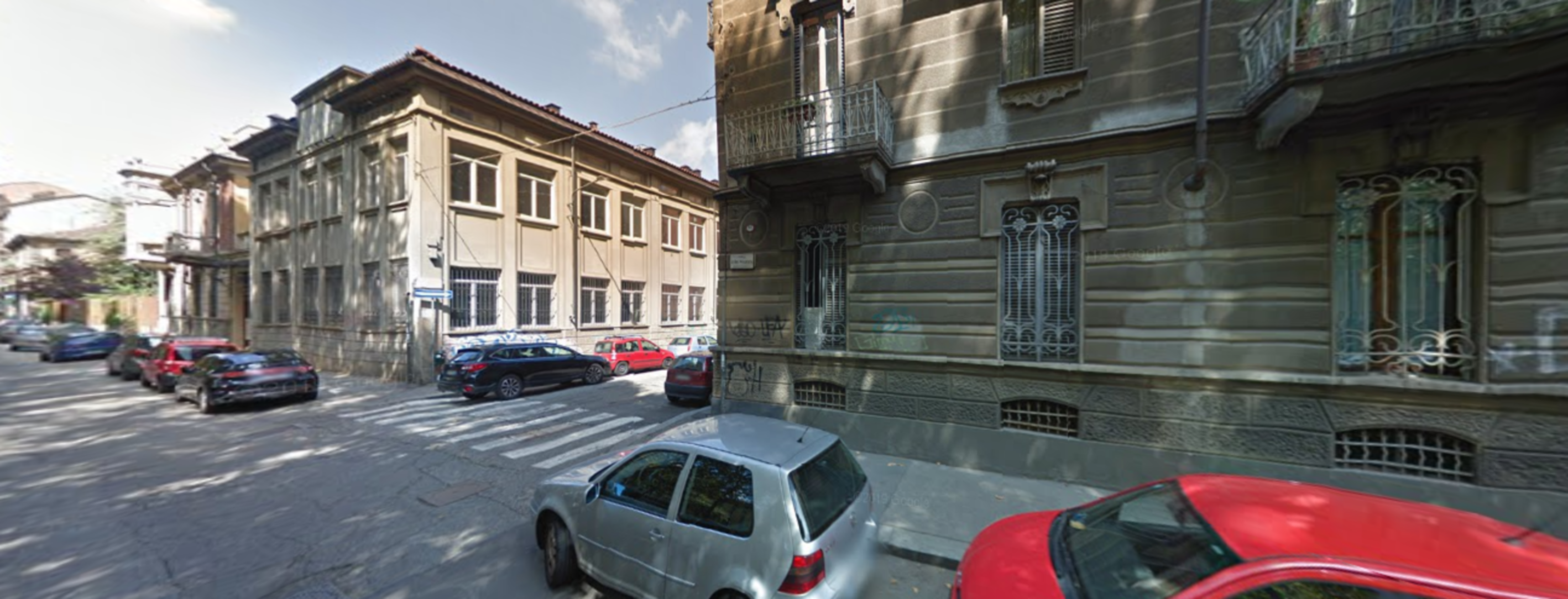 A car parked in front of a building at B&B Turin.