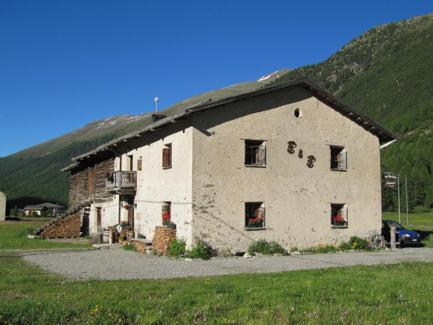 A large brick building with a mountain in the background at Bed & Breakfast Campaciol.