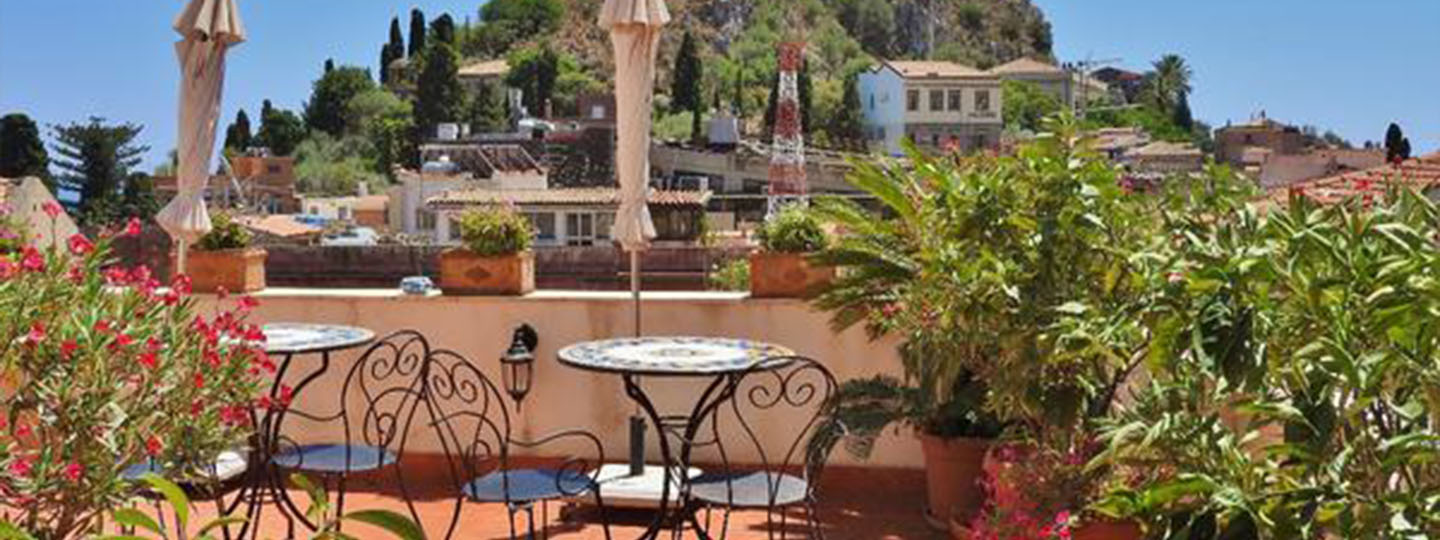 A group of palm trees with a building in the background at Cielo di Taormina.