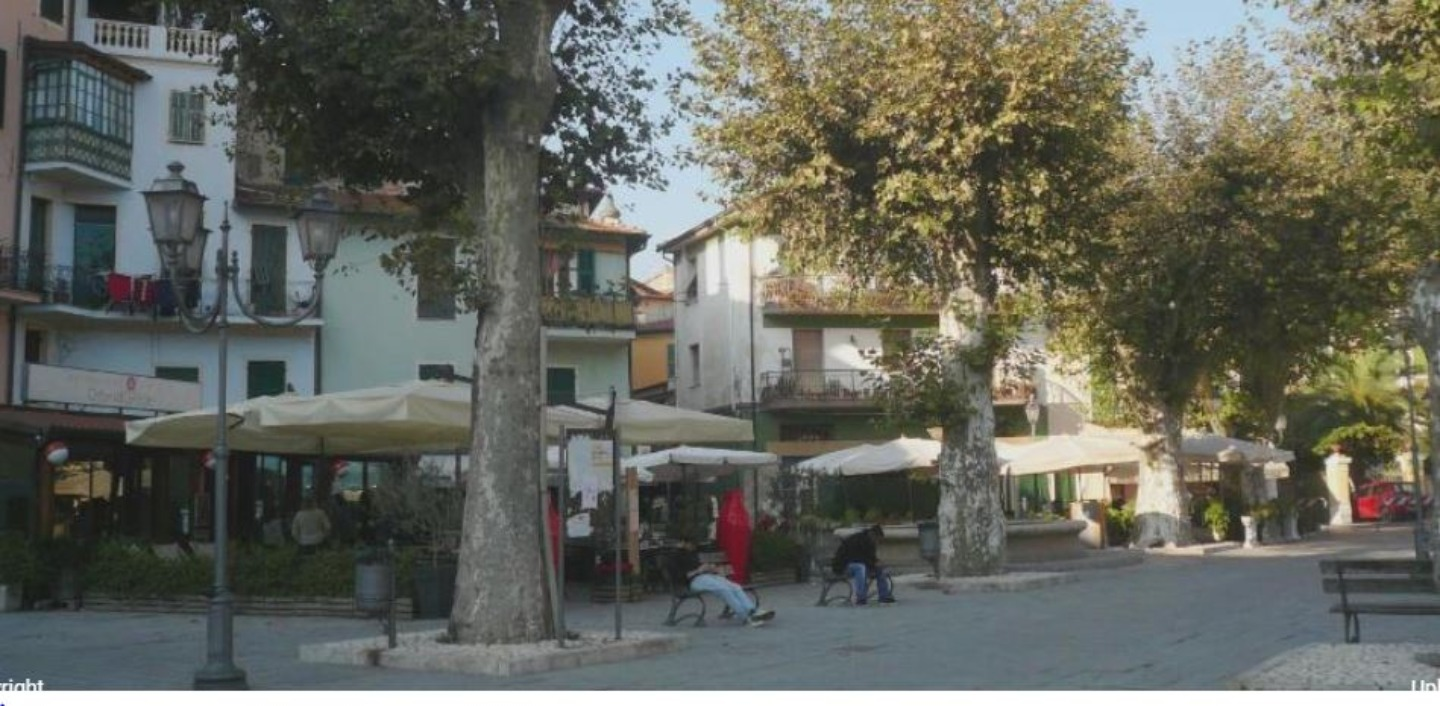 A group of people walking down a street next to a tree at B&B Dei Doria.