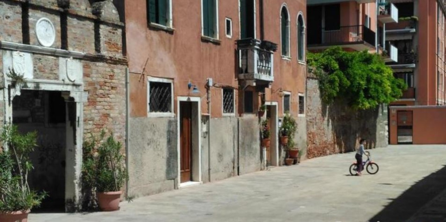 A person walking down a street in front of a brick building at B&B Dorsoduro461.