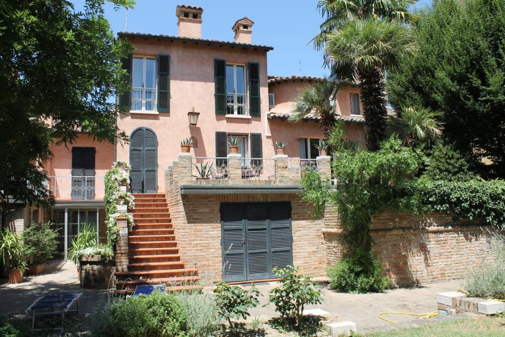 A house with bushes in front of a brick building at Ai Giardini San Vitale.