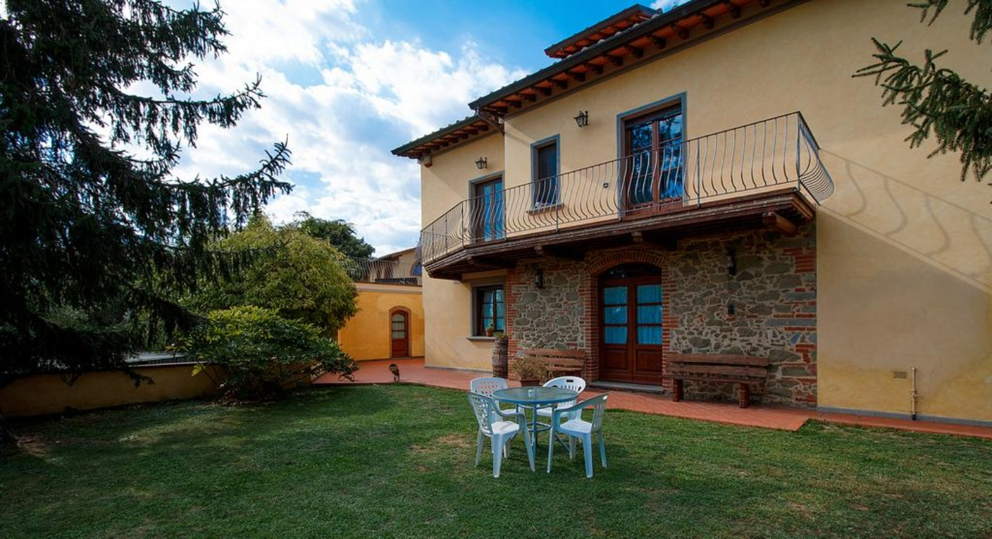 A large lawn in front of a house at AGRITURISMO IL PIASTRINO.