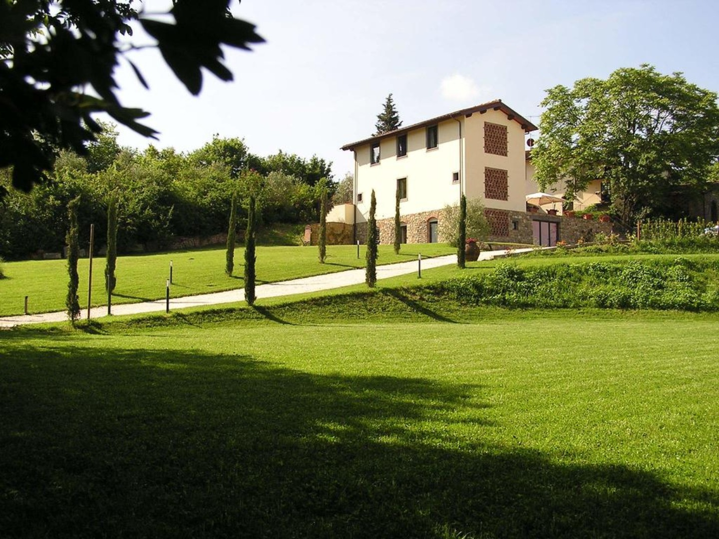 A large green field with trees in the background at Il Poggiolo delle Rose.