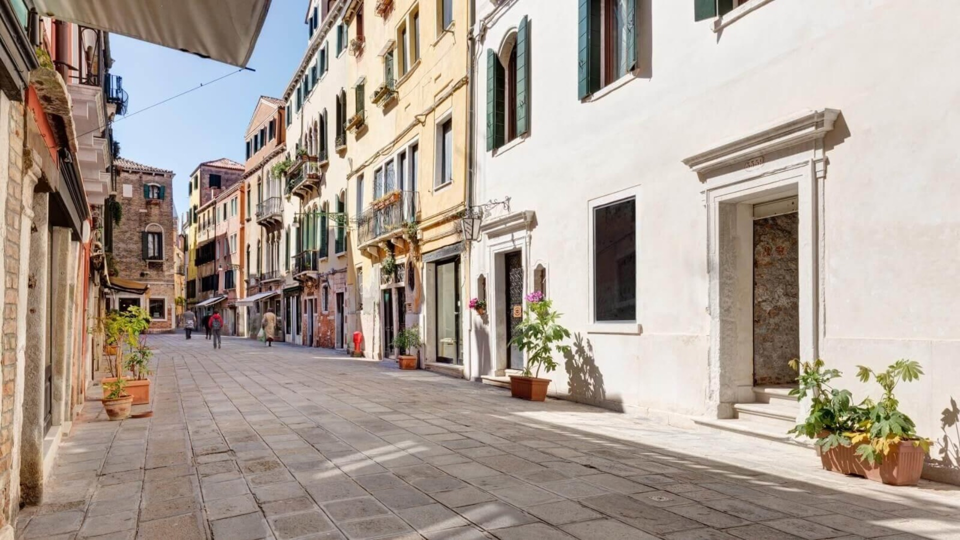 A person walking down a street next to a building at Hotel San Samuele.