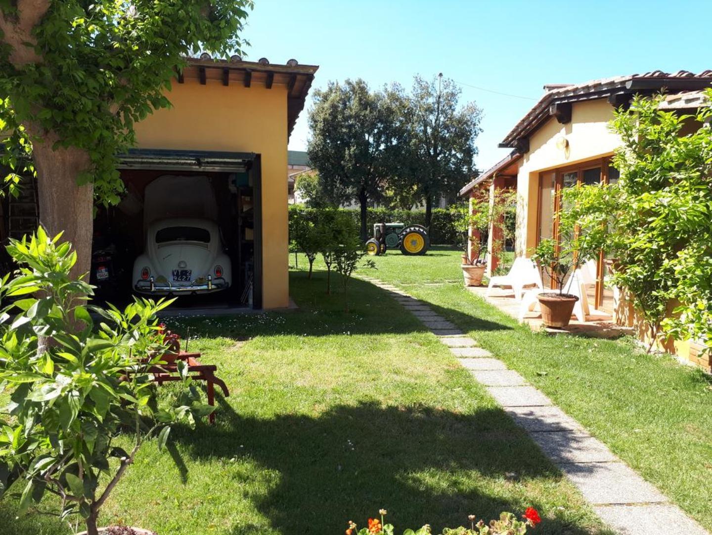 A large lawn in front of a house at La Corte di Stelio B&B.