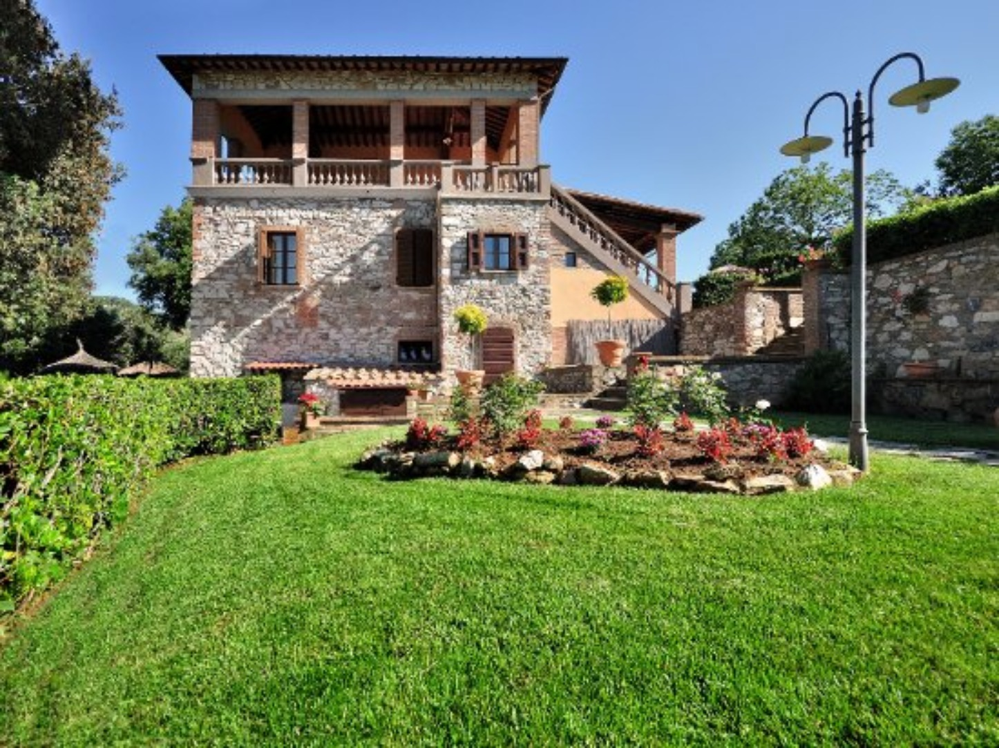 A large brick building with grass in front of a house at Il Castagno Toscana.