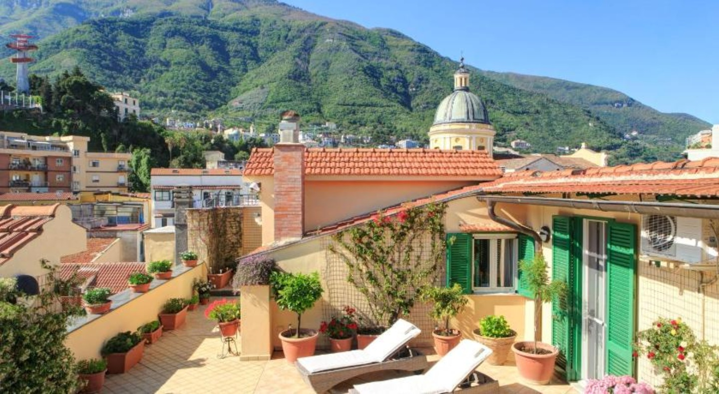 A large building with a mountain in the background at Tetto Fiorito.
