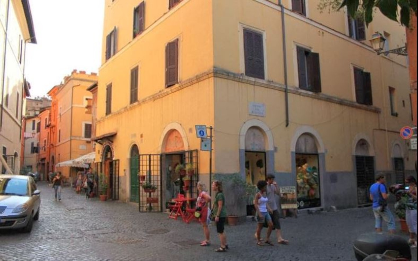 A group of people walking in front of a building at Ventisei Scalini a Trastevere.