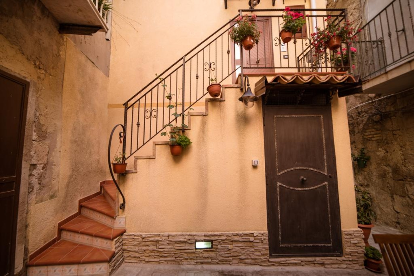 A narrow hallway with graffiti on the side of a building at Marchese Sant' Andrea B&B.