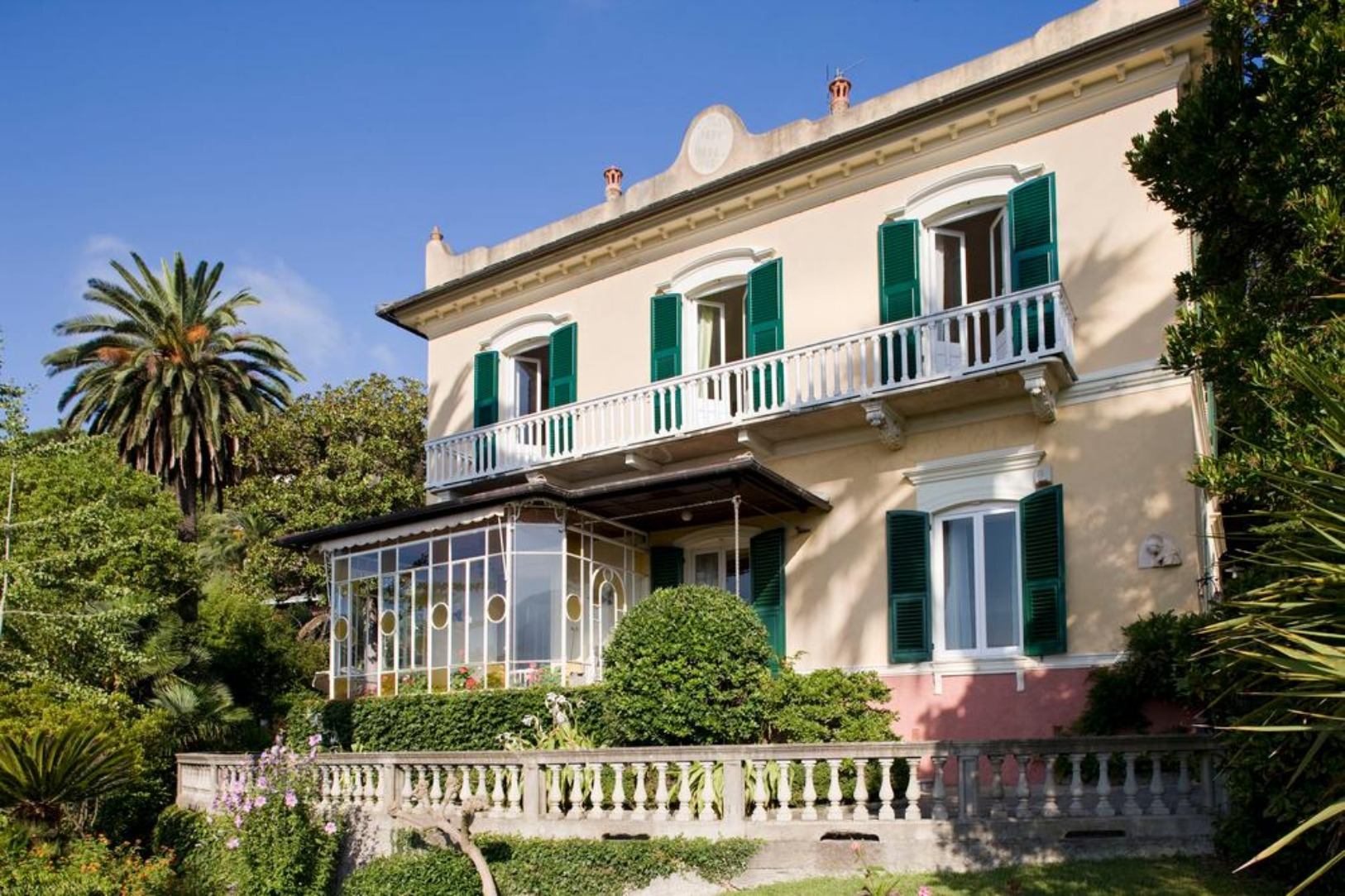 A house with bushes in front of a building at Villa Olimpo.