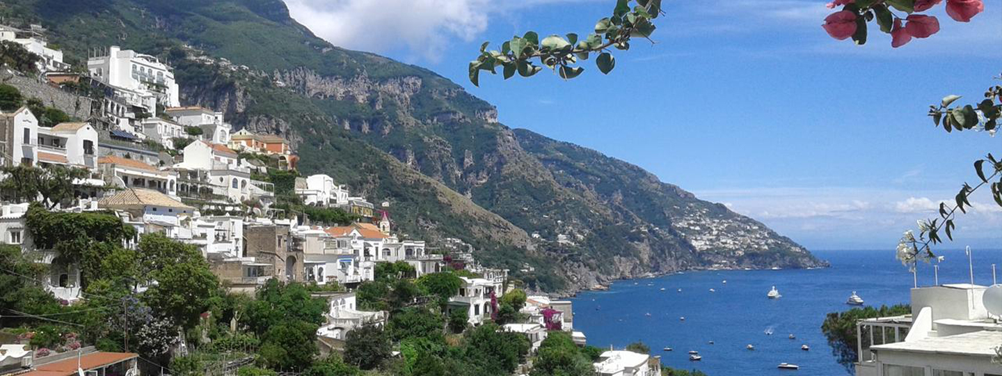 A large body of water with a mountain in the background at Venus Inn B&B in Positano.