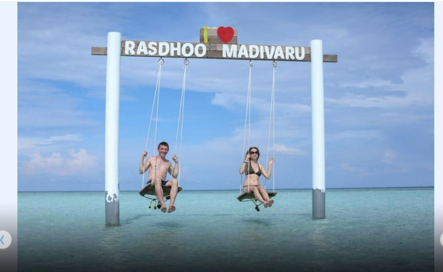 A person standing next to a body of water at Rasreef Maldives.