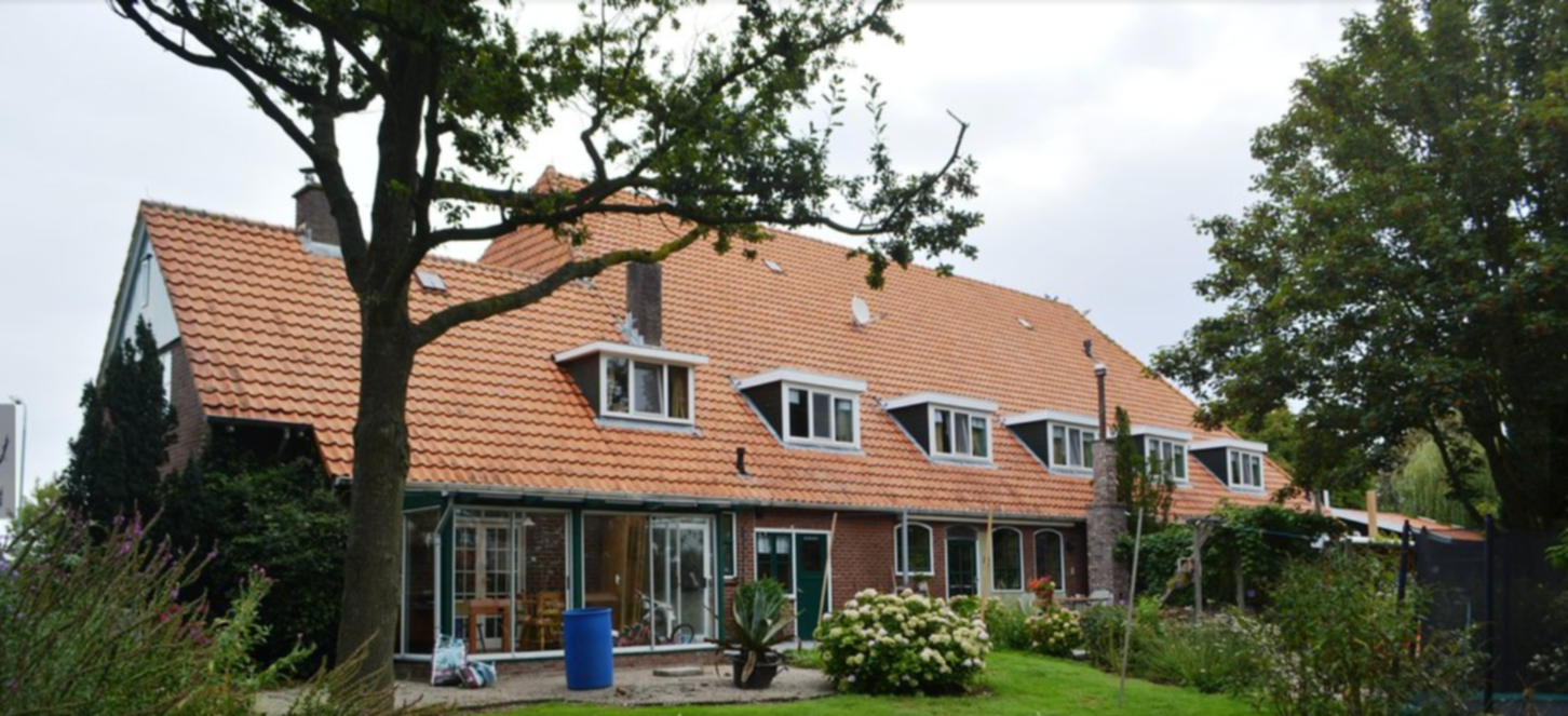 A large brick building with grass in front of a house at B&B De Nieuwe Tijd.