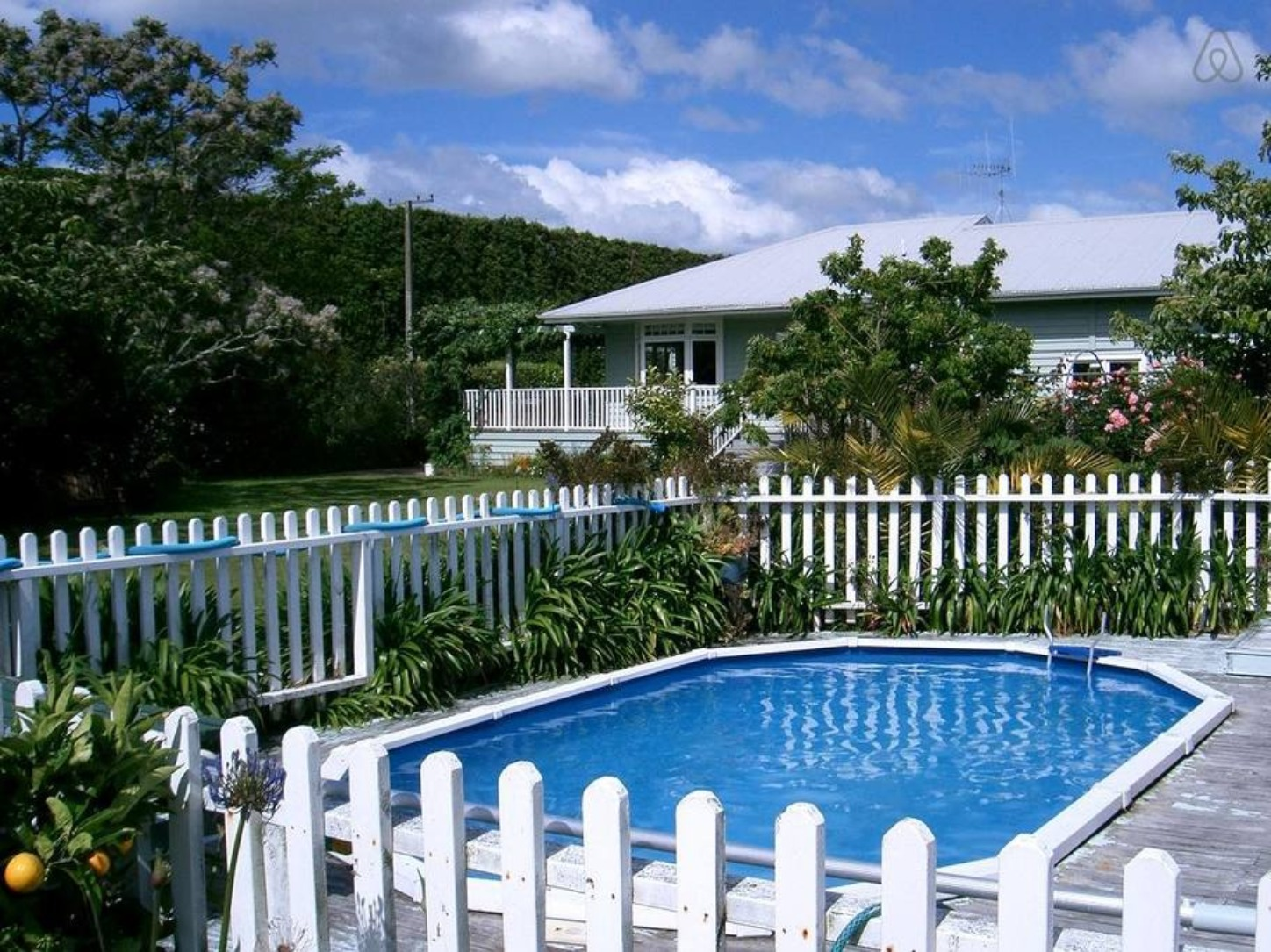 A group of lawn chairs sitting next to a pool at Aotea Villa.