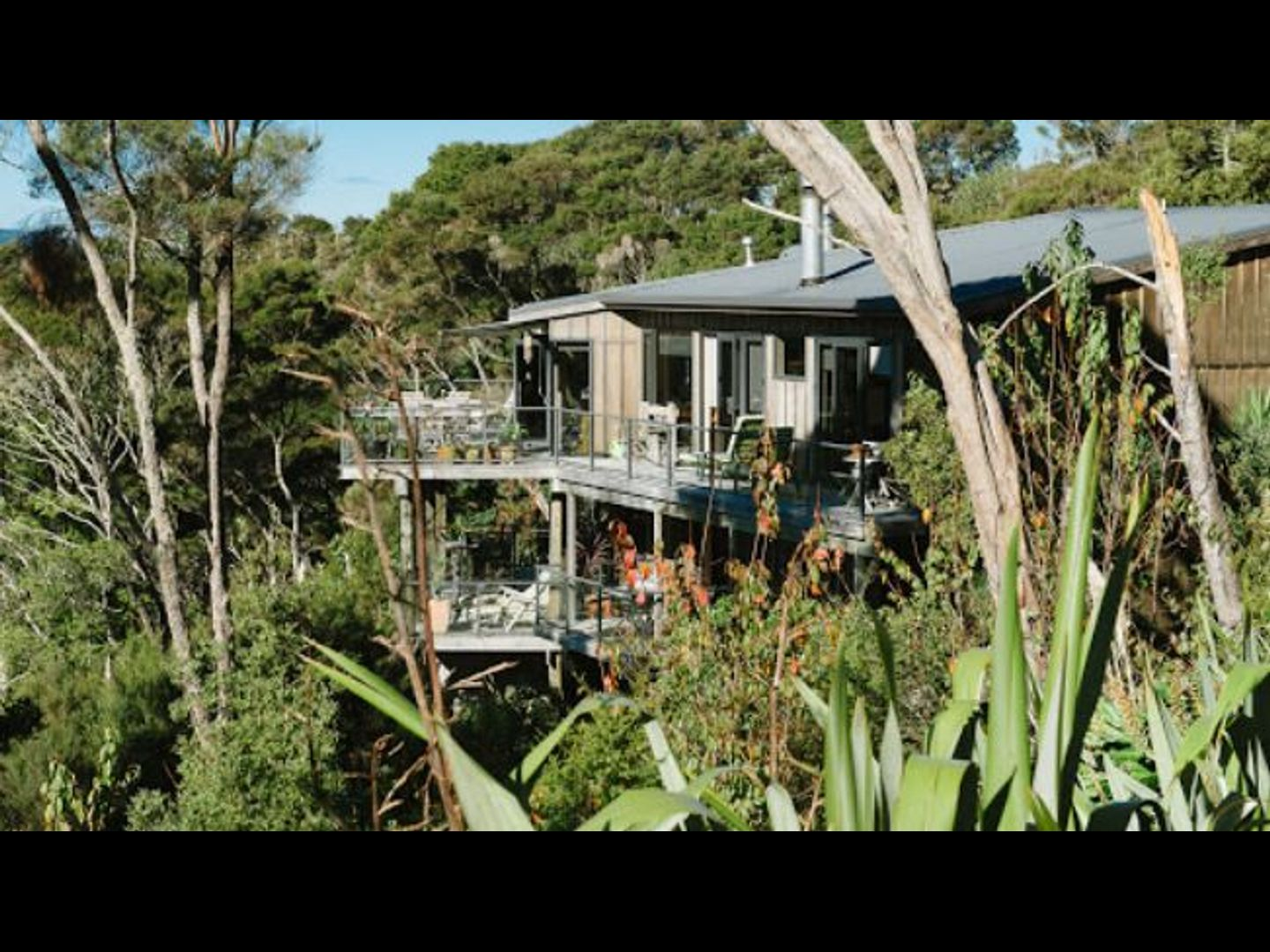 A house with bushes in the background at The Sanctuary at Bay of Islands Lodge.