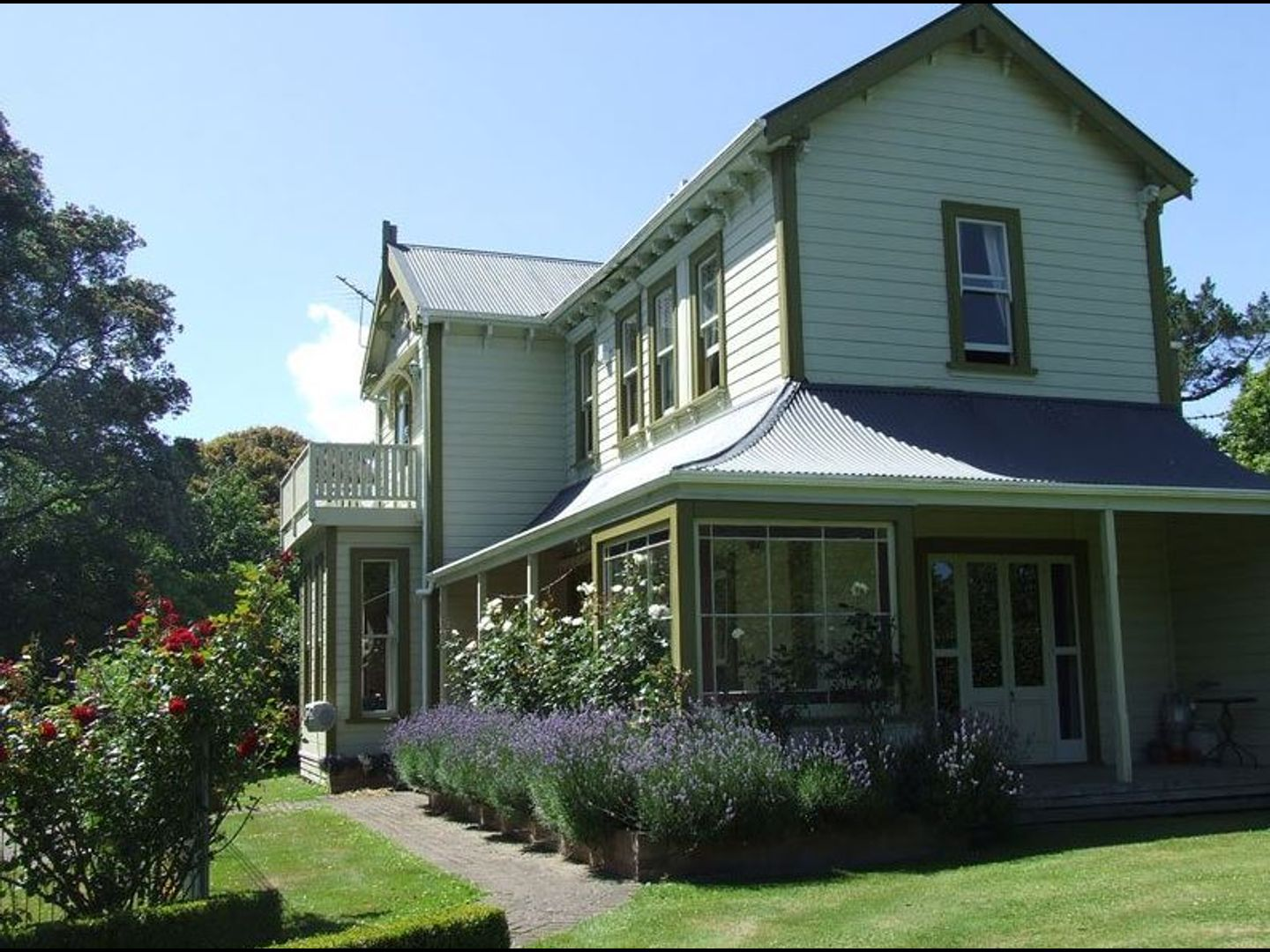 A house with bushes in front of a building at Tairoa Lodge & Cottage.