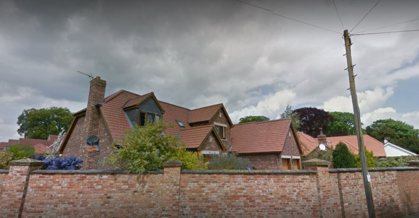 A house with trees in the background at Allington Manor.