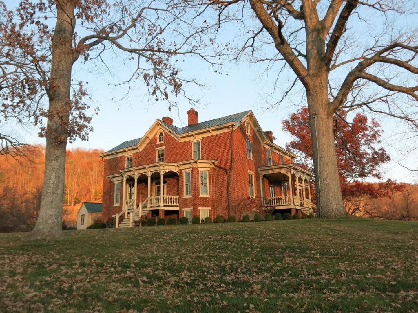 A large brick building with grass in front of a house at The Inn at Mount Vernon Farm.