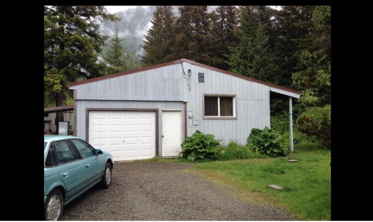 A car parked in front of a house at Juneau Guest House.