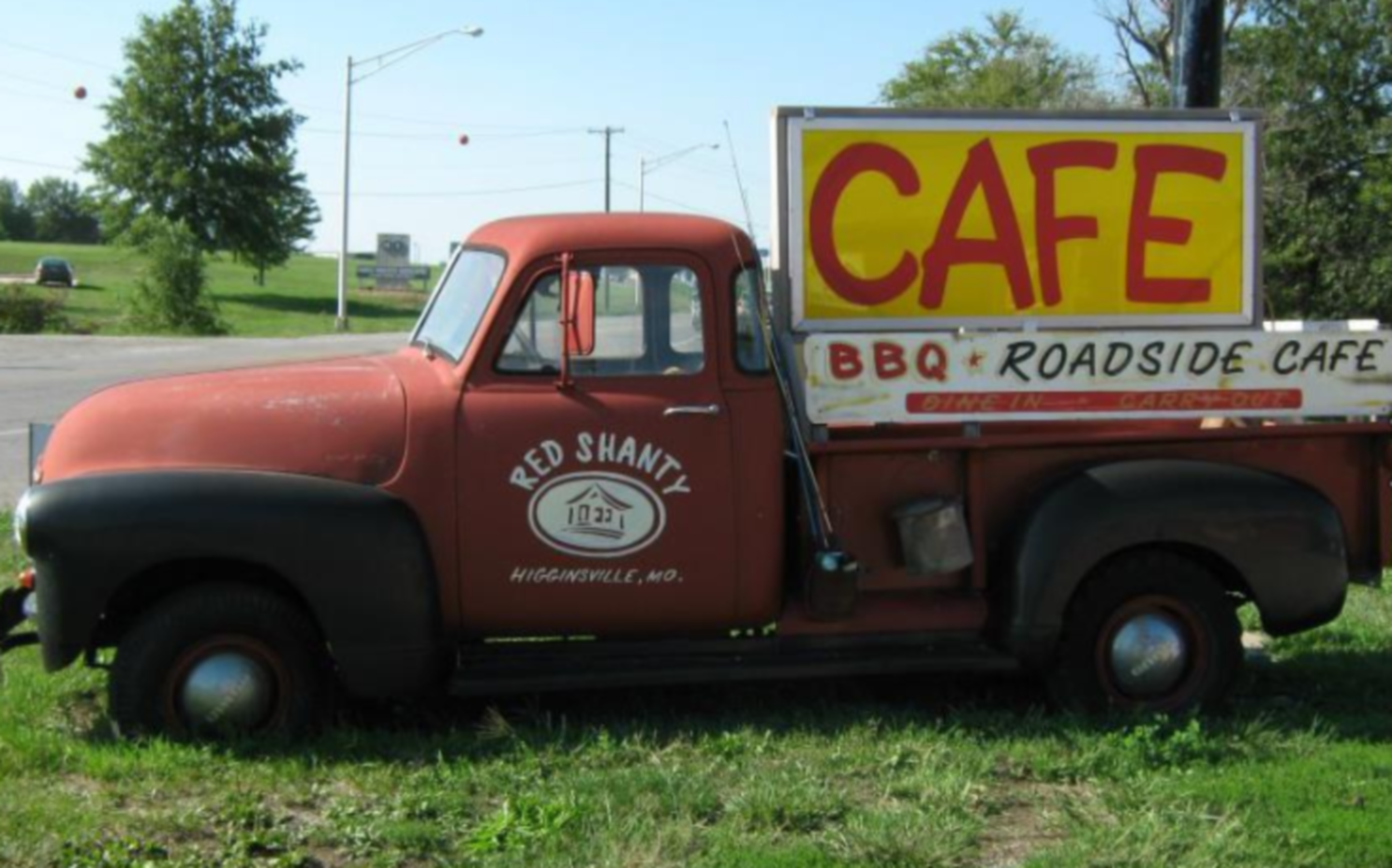 A truck is parked in the grass at Red Shanty BBQ & Roadside Cafe.