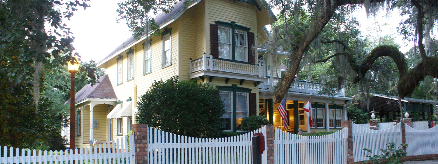 A house with a fence in front of a building at Avera-Clarke House Bed & Breakfast.